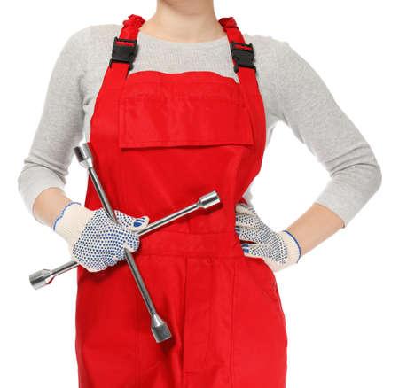 Female auto mechanic with lug wrench on white background, closeup