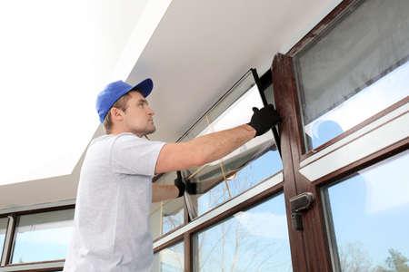 Construction worker repairing window in house