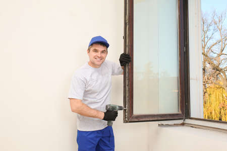 Construction worker repairing window in house