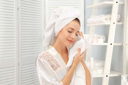 Young woman wiping her face with towel in bathroom