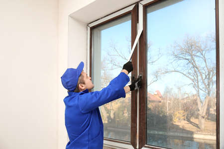 Construction worker removing sticky tape from window frame in house