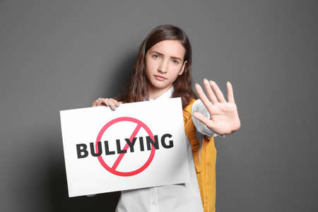 Teenage girl holding sign with crossed word Bullying on grey background
