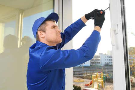 Bauarbeiter, der Fenster im Haus repariert Standard-Bild