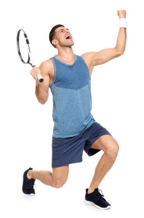 Portrait of handsome man playing tennis against white background