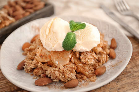 Plate with apple crisp and ice cream on table, closeup