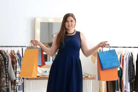 Beautiful overweight woman with shopping bags in boutique