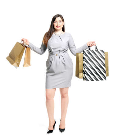 Beautiful overweight woman with shopping bags on white background