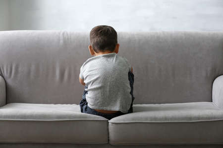 Little boy sitting on sofa at home. Child autism 免版税图像