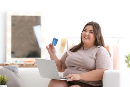 Beautiful overweight woman with laptop and credit card indoors