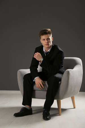 Handsome man in formal suit sitting against grey wall
