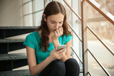 Upset teenage girl with smartphone indoors. Cyber bullying 免版税图像