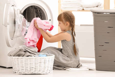 Cute little girl doing laundry indoors Imagens