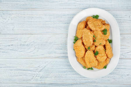 Plate with tasty chicken nuggets on table