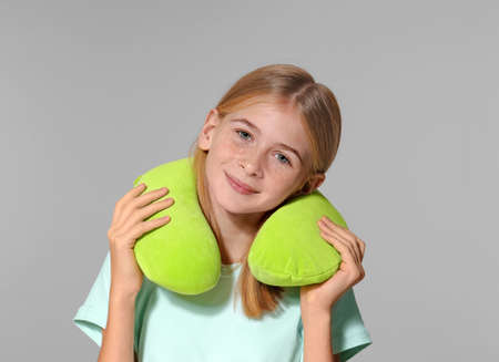 Cute girl with travel pillow on grey background Stock Photo