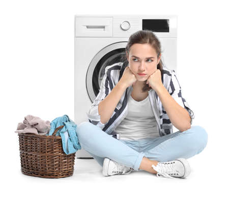Woman with laundry basket near washing machine on white background