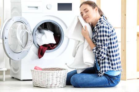 Jeune femme faisant la lessive à la maison Banque d'images