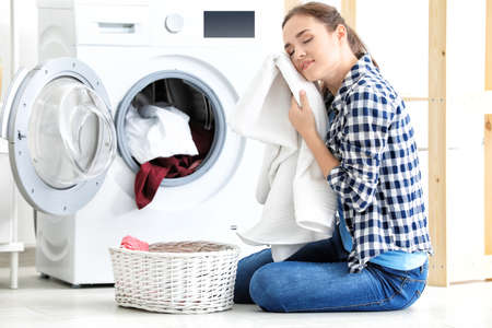 Mujer joven lavando ropa en casa Foto de archivo - 100566432