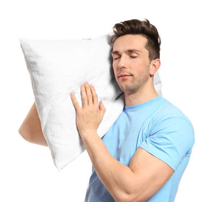Young man with soft pillow on white background