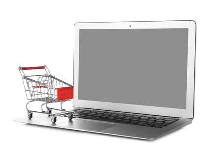Laptop and small cart on white background. Internet shopping concept