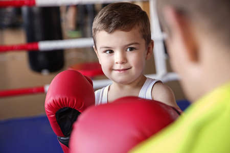 Little boy training with coach in boxing ring