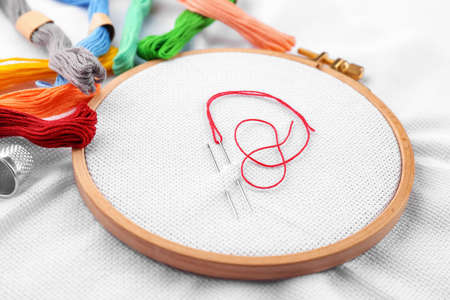 Embroidery hoop with fabric, sewing needles and thread, closeup