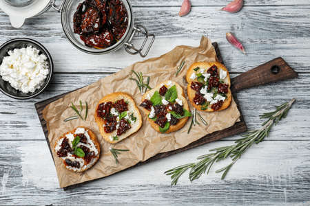 Tasty bruschettas with sun-dried tomatoes on wooden board, top view