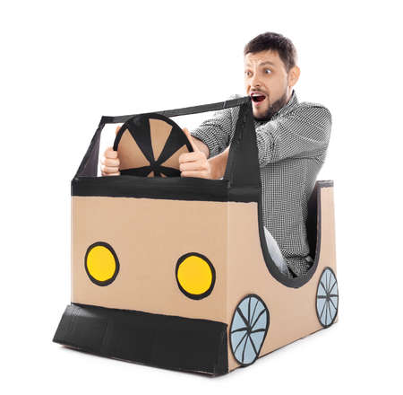 Young man dreaming of buying own auto while playing with cardboard car on white background