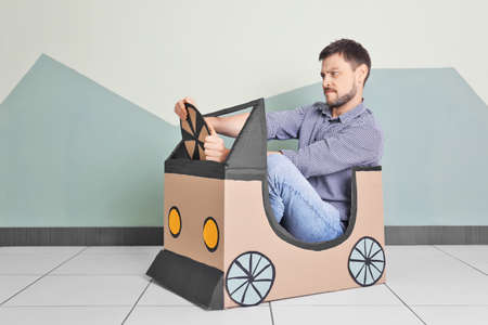 Young man dreaming of buying own auto while playing with cardboard car indoors