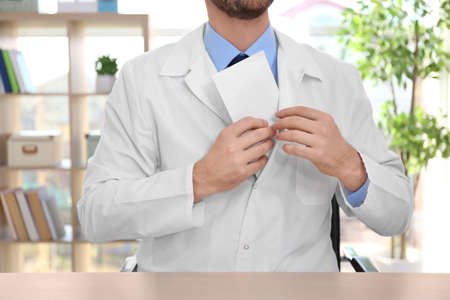 Male doctor putting bribe in pocket at workplace Stock Photo