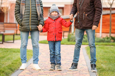 Male gay couple with adopted boy outdoors Фото со стока