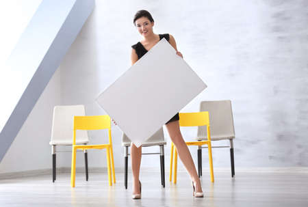 Young woman with blank advertising board indoors