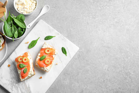 Delicious bruschettas with salmon and olives on marble board