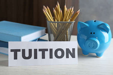Paper with word TUITION and piggy bank on table Stock Photo