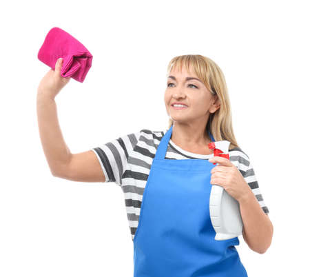 Portrait of mature woman in apron with detergent and rag on white background Stock Photo