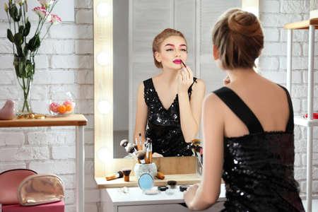 Giovane bella donna che applica trucco vicino allo specchio in camera Archivio Fotografico - 100528980