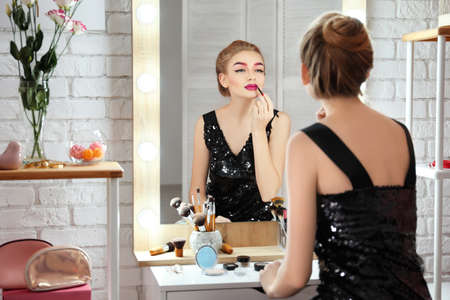Young beautiful woman applying makeup near mirror in room