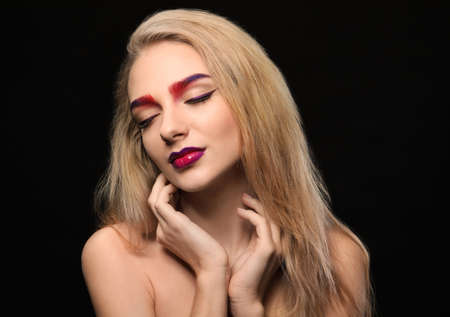 Young woman with dyed eyebrows on black background Stock Photo
