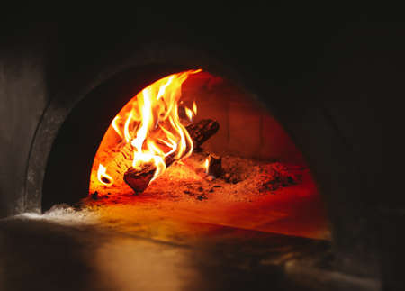 Burning firewood in traditional oven at restaurant kitchen Stock Photo