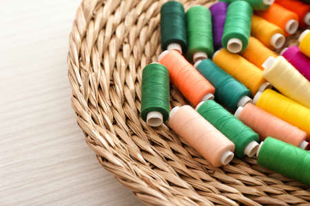 Heap of color sewing threads on wicker plate Stock Photo