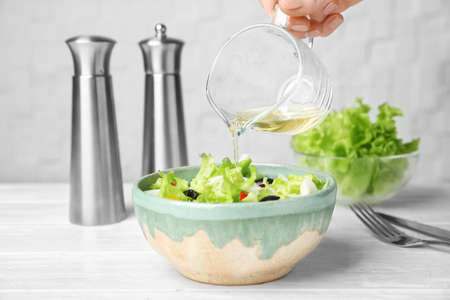 Woman adding tasty apple vinegar into salad with vegetables on table