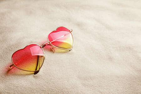 Glasses in shape of heart on white sand