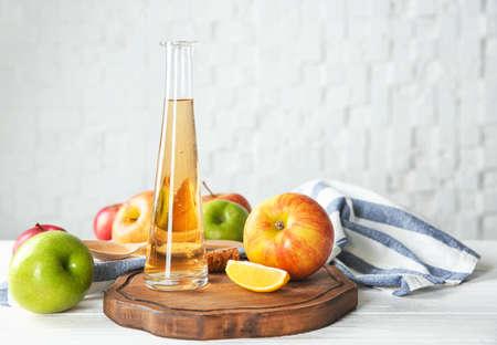 Glass bottle with apple vinegar and fresh fruit on table