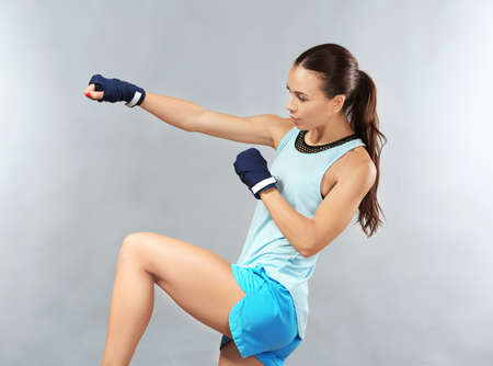 Strong boxer woman on grey background