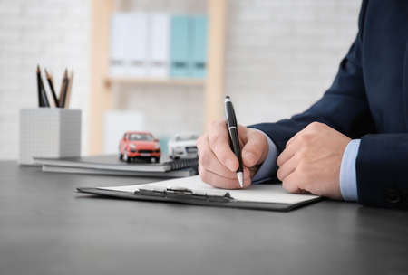 Mężczyzna wypełniający formularz ubezpieczenia samochodu przy stole