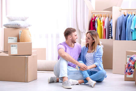 Young couple resting near wardrobe boxes on moving day