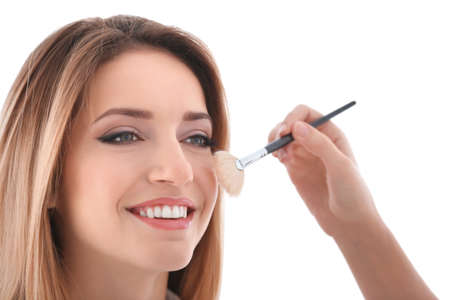 Professional artist creating makeup for model on white background