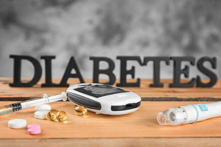 Digital glucometer, medicaments and blurred word Diabetes on background Stock Photo