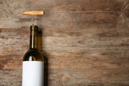 Bottle of wine with corkscrew and blank label on wooden background. Mock up for design