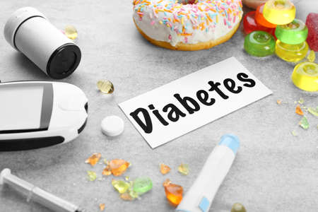 Composition with word Diabetes, glucometer, medicaments and treats on grey background 写真素材