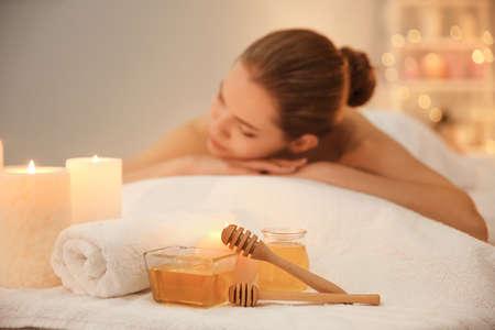 Miel pour les procédures de spa et jeune femme en salon
